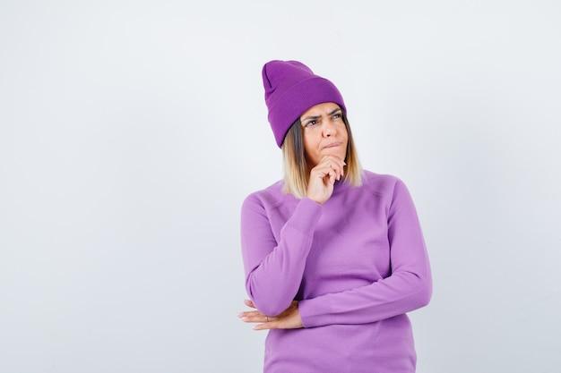 Jovem senhora de suéter roxo, gorro apoiando o queixo na mão e olhando pensativa, vista frontal.