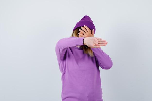 Jovem senhora de suéter roxo, gorro mostrando o gesto de parada enquanto com a mão no rosto e olhando confiante, vista frontal.