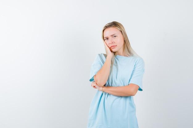 Jovem senhora descansando o rosto na mão na camiseta e olhando pensativa, vista frontal.