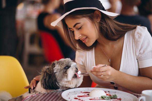 Jovem senhora em bar com cachorro fofo almoçando