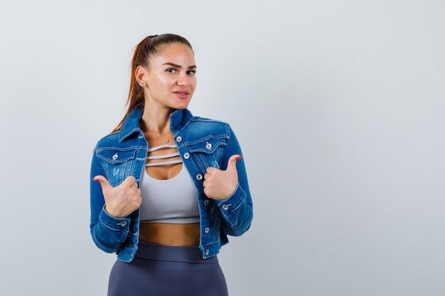 Jovem senhora em cima, jaqueta jeans aparecendo os polegares e olhando alegre, vista frontal.