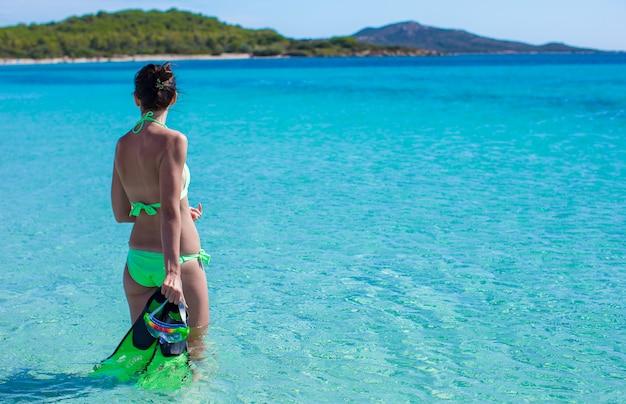 Jovem senhora em mar azul tropical com equipamento de mergulho no dia ensolarado