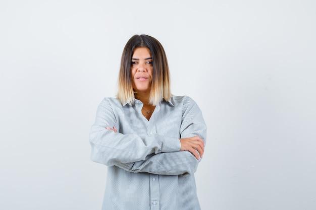 Jovem senhora em pé com os braços cruzados em uma camisa grande e parecendo confiante, vista frontal.