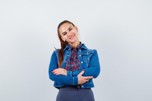 Jovem senhora em pé com os braços cruzados na camisa quadriculada, jaqueta jeans e olhando alegre, vista frontal.