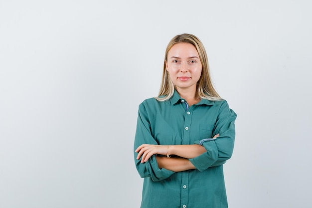 Jovem senhora em pé com os braços cruzados na camisa verde e parecendo confiante.