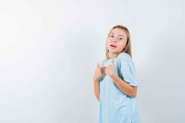 Jovem senhora em t-shirt, apontando para si mesma e orgulhosa, vista frontal.