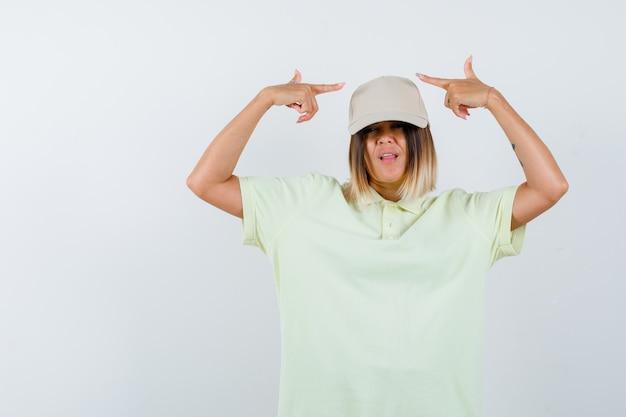 Jovem senhora em t-shirt, boné apontando para os dois lados e parecendo confiante, vista frontal.