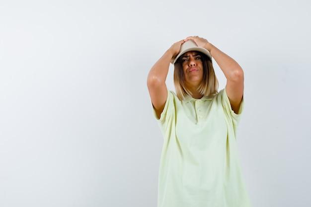 Jovem senhora em t-shirt, boné de mãos dadas na cabeça e olhando esquecido, vista frontal.