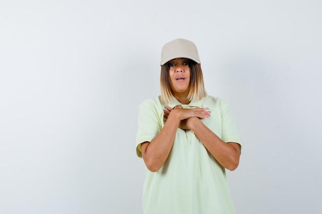 Jovem senhora em t-shirt, boné de mãos dadas no peito e parecendo perplexo, vista frontal.