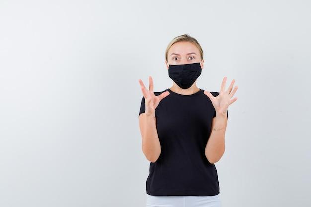 Jovem senhora em t-shirt, calça, máscara médica, mantendo as mãos de forma agressiva