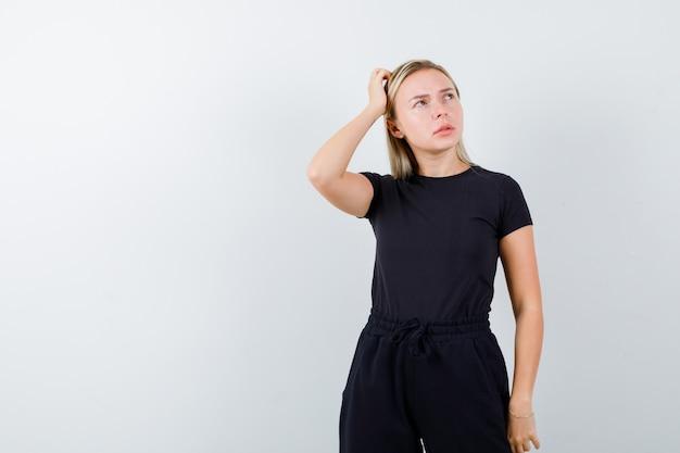 Jovem senhora em t-shirt, calças, segurando a mão na cabeça e olhando pensativa, vista frontal.