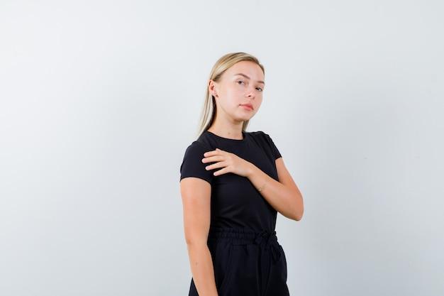 Jovem senhora em t-shirt, calças, segurando a mão no peito e parecendo confiante, vista frontal.