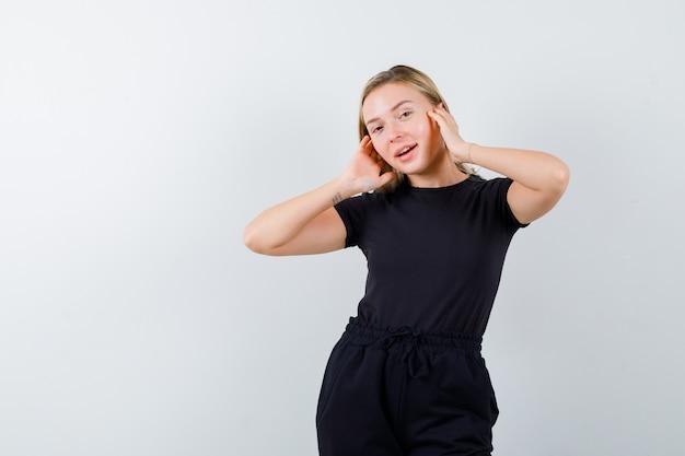 Jovem senhora em t-shirt, calças segurando as mãos nas orelhas e olhando alegre, vista frontal.