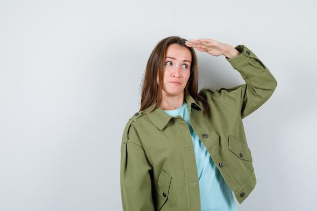 Jovem senhora em t-shirt, casaco com as mãos na cabeça para ver claramente e parecendo confiante, vista frontal.