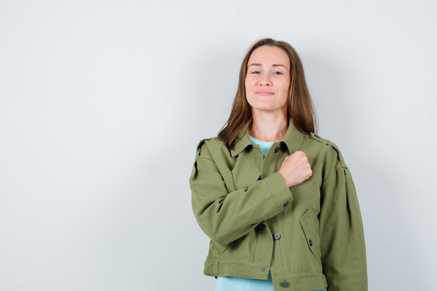 Jovem senhora em t-shirt, casaco com punho no peito e parecendo confiante, vista frontal.