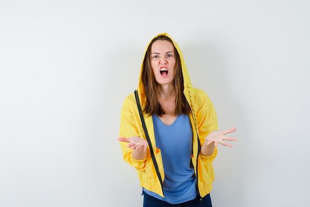 Jovem senhora em t-shirt, casaco, mantendo as mãos de forma agressiva, vista frontal.