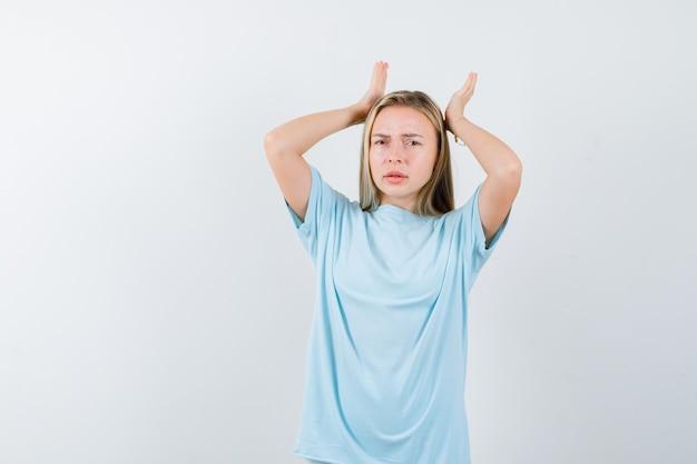 Jovem senhora em t-shirt de mãos dadas na cabeça e parecendo cansada, vista frontal.