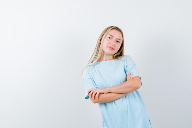 Jovem senhora em t-shirt em pé com os braços cruzados e olhando confiante, vista frontal.