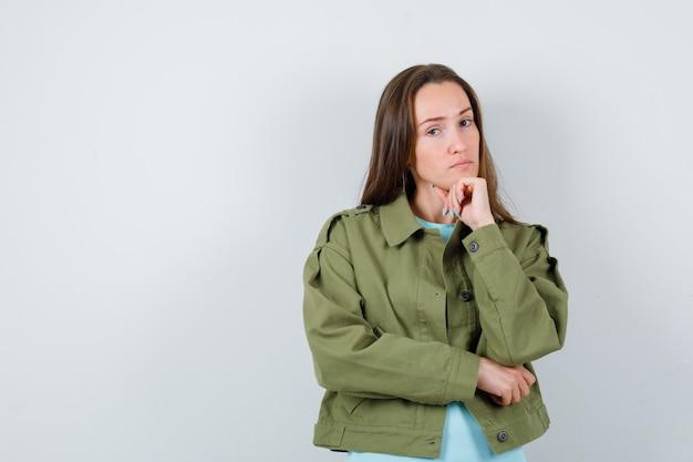 Jovem senhora em t-shirt, jaqueta, apoiando o queixo no punho e parecendo confiante, vista frontal.