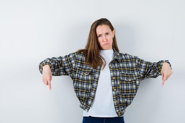 Jovem senhora em t-shirt, jaqueta apontando para baixo e parecendo triste, vista frontal.