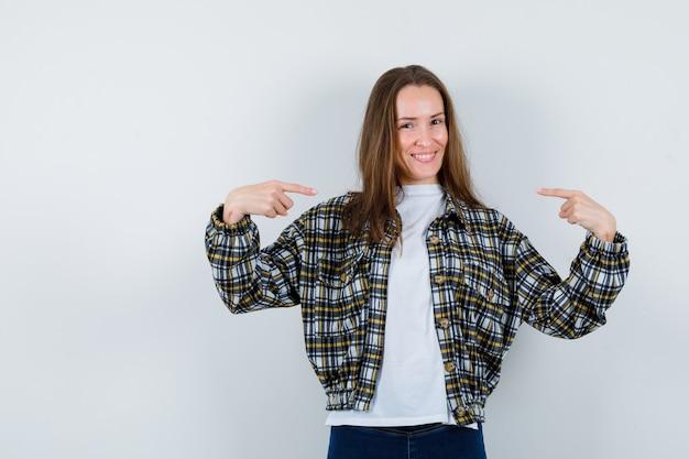 Jovem senhora em t-shirt, jaqueta, apontando para si mesma e parecendo orgulhosa, vista frontal.