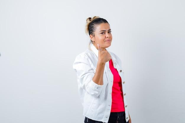 Jovem senhora em t-shirt, jaqueta branca aparecendo o polegar e parecendo satisfeita, vista frontal.