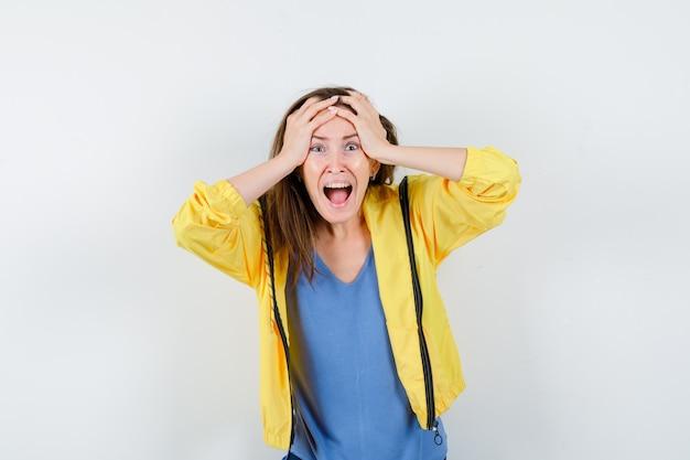 Jovem senhora em t-shirt, jaqueta de mãos dadas na cabeça e parecendo impotente, vista frontal.