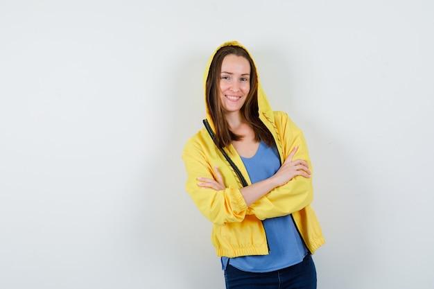 Jovem senhora em t-shirt, jaqueta em pé com os braços cruzados e olhando alegre, vista frontal.