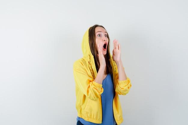 Jovem senhora em t-shirt, jaqueta gritando ou anunciando algo e parecendo animada, vista frontal.