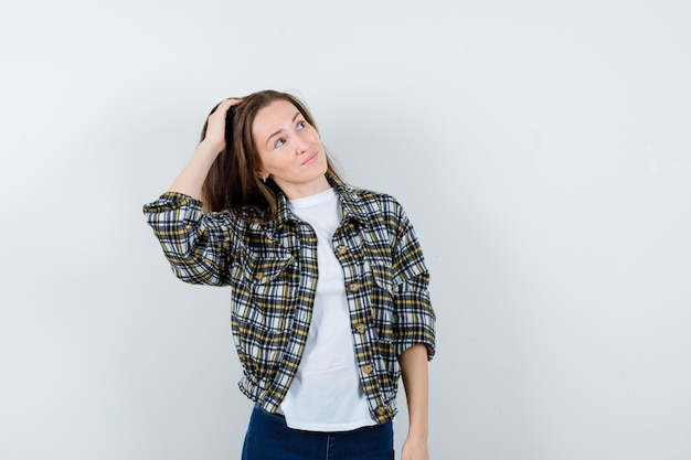Jovem senhora em t-shirt, jaqueta, jeans, penteia o cabelo com a mão enquanto olha para cima e parece atraente, vista frontal.