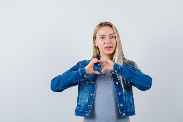 Jovem senhora em t-shirt, jaqueta jeans, saia mostrando gesto de coração e está linda
