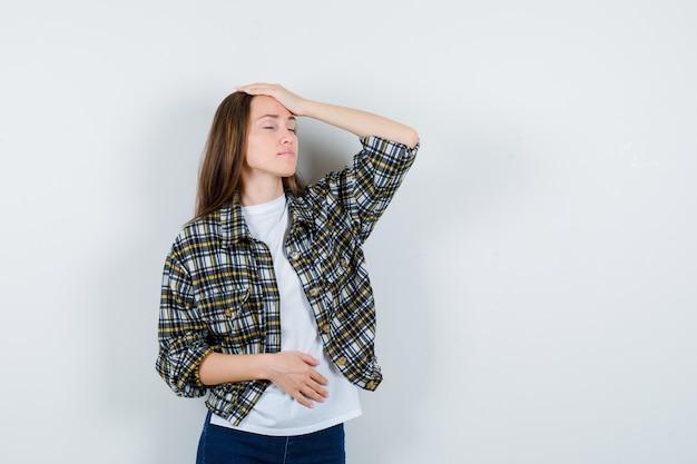 Jovem senhora em t-shirt, jaqueta, jeans, segurando a mão na cabeça e parecendo esquecida, vista frontal.