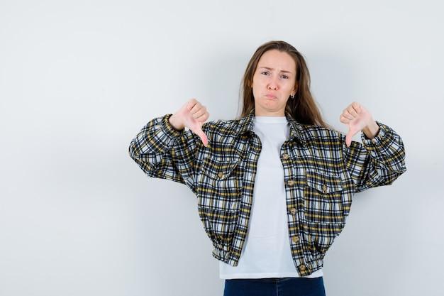 Jovem senhora em t-shirt, jaqueta mostrando dois polegares para baixo e parecendo triste, vista frontal.