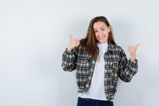Jovem senhora em t-shirt, jaqueta mostrando dois polegares para cima e parecendo feliz, vista frontal.