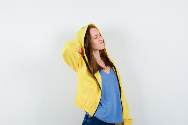 Jovem senhora em t-shirt, jaqueta, sofrendo de dor no pescoço e parecendo cansada, vista frontal.