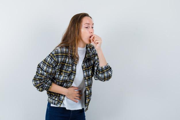 Jovem senhora em t-shirt, jaqueta, sofrendo de tosse e parecendo doente, vista frontal.