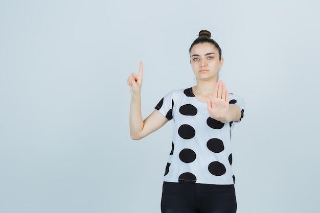 Jovem senhora em t-shirt, jeans apontando para cima enquanto mostra o gesto de parar e olhando séria, vista frontal.