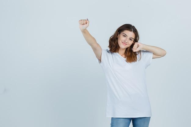 Jovem senhora em t-shirt, jeans, mostrando o gesto de vencedor e parecendo feliz, vista frontal.