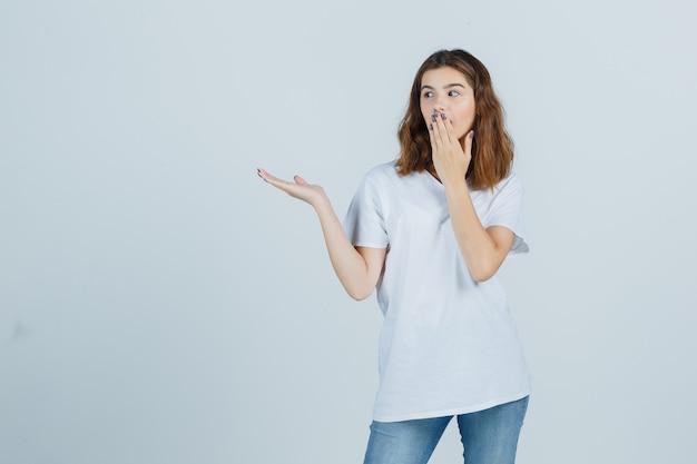 Jovem senhora em t-shirt, jeans, segurando a mão na boca enquanto mostra algo e parece confusa, vista frontal.