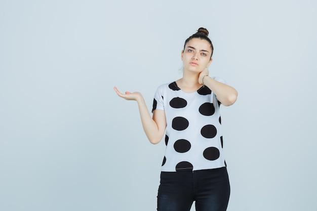 Jovem senhora em t-shirt, jeans, segurando a mão no pescoço enquanto finge segurar algo e parece pensativa, vista frontal.