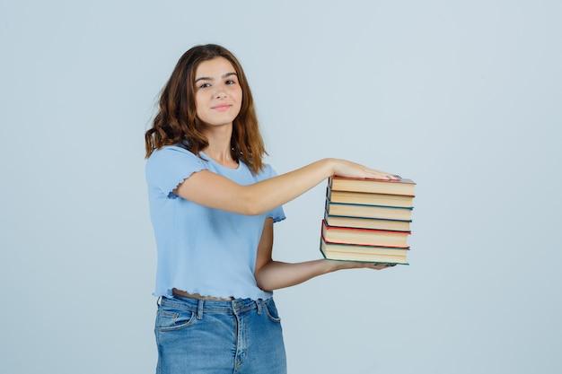 Jovem senhora em t-shirt, jeans, segurando livros e parecendo satisfeita, vista frontal.
