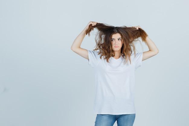 Jovem senhora em t-shirt, jeans, segurando uma mecha de cabelo e olhando engraçado, vista frontal.