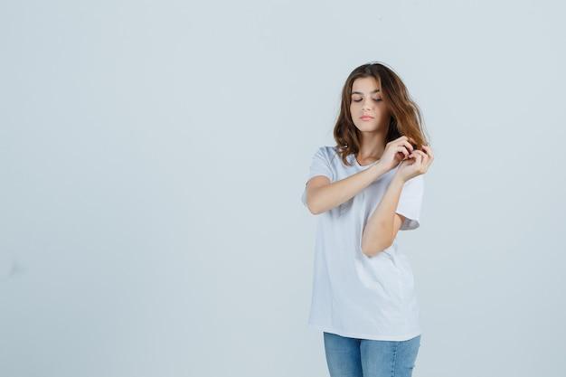 Jovem senhora em t-shirt, jeans, segurando uma mecha de cabelo e olhando pensativa, vista frontal.