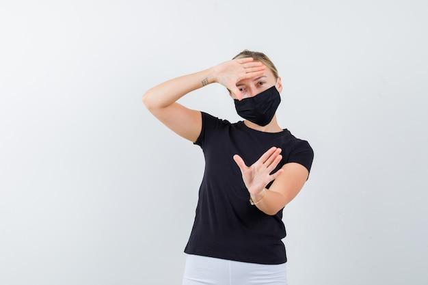 Jovem senhora em t-shirt preta, máscara fazendo gesto de quadro e olhando alegre, vista frontal.
