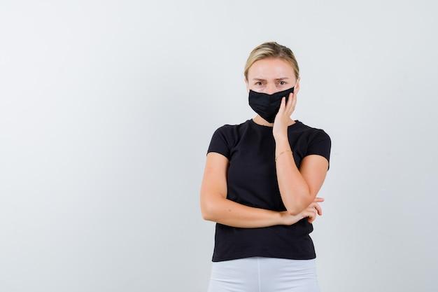 Jovem senhora em t-shirt preta, máscara, mantendo a mão na bochecha e parecendo chateada, vista frontal.