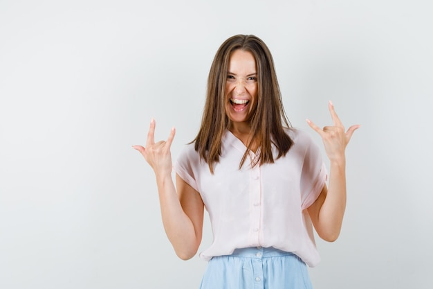Jovem senhora em t-shirt, saia mostrando o gesto 'eu te amo' e parecendo louca, vista frontal.
