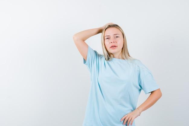 Jovem senhora em t-shirt, segurando a mão na cabeça, mantendo a mão na cintura e olhando pensativa, vista frontal.