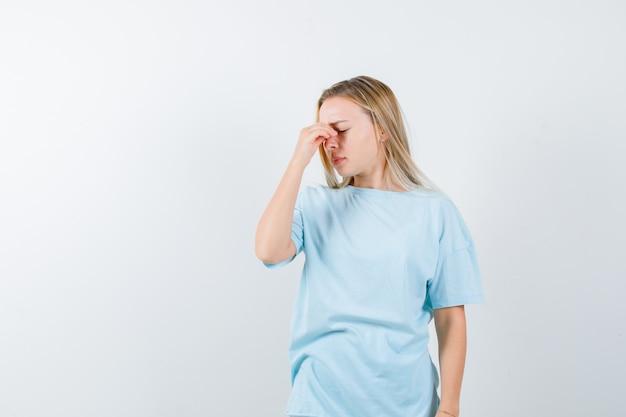Jovem senhora em t-shirt, sofrendo de dor de cabeça e parecendo exausta, vista frontal.