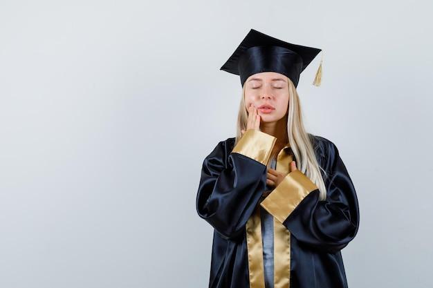 Jovem senhora em trajes acadêmicos, sofrendo de dor de dente e parecendo indisposta