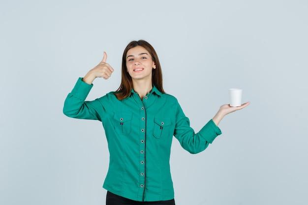 Jovem senhora em uma camisa segurando um copo plástico de café enquanto aparecia o polegar e olhando alegre, vista frontal.